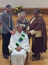 Jim Marsh being prayer over by his mom and friends during recent ordination