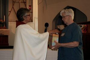 Marion Flynn of the Women's Ordination Conference presents newly ordained priest, Tee Rigodanzo-Kasper with glass chalice.